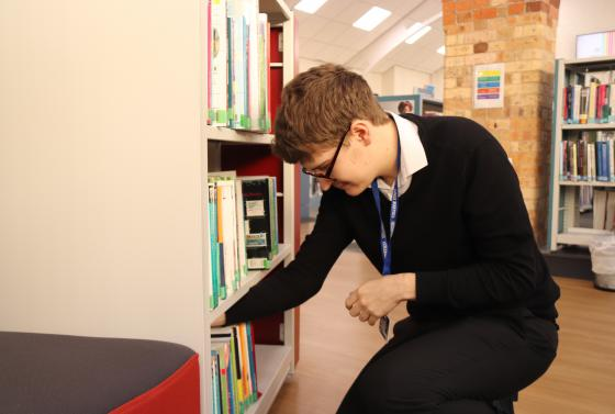Business apprentice putting books away on shelf
