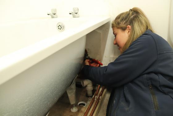 Plumbing apprentice working on a bath