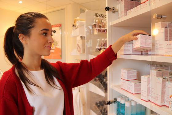 Beauty apprentice stocking shelves in beauty salon