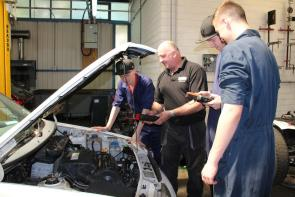 a tutor and students in a motor vehicle workshop