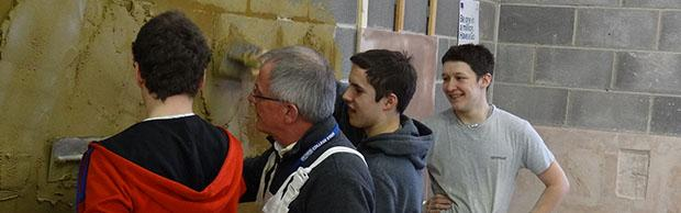 Plastering students being instructed by tutor