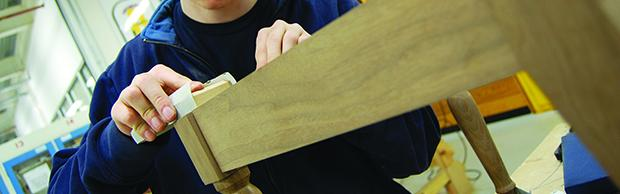 Student sanding wooden furniture